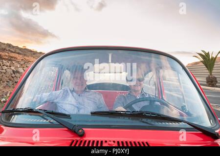 Schön nach paar Antrieb und Liebe in einem roten alten Vintage Auto auf der Straße geparkt werden. lächeln und Spaß haben, die zusammen reisen. Glück und Lebensstil für - Stockfoto