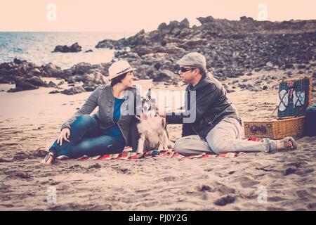 Gruppe sehr netter Hund, Mann und Frau, Junge Leute Spaß zusammen mit dem Picknick am Strand und genießen Sie die Freizeit im Freien. Mode Leute - Stockfoto