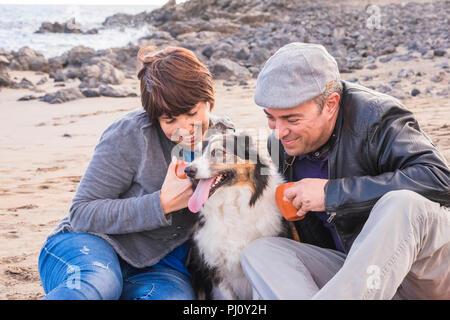 Gruppe sehr netter Hund, Mann und Frau, junge Menschen gemeinsam Spaß am Strand Tee trinken und genießen die Outdoor Freizeitaktivitäten Aktivität. Mode Leute - Stockfoto