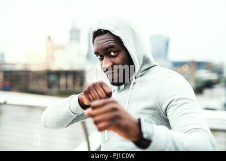 Junge aktive schwarze Sportler im Boxen Position in einer Stadt, hoodie tragen. - Stockfoto