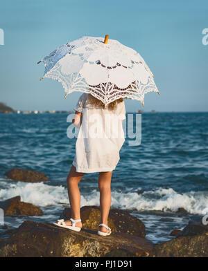 Kleines Mädchen mit Schirm in der Nähe des Meeres - Stockfoto