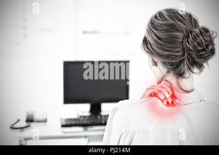 Das zusammengesetzte Bild der Rückseite eine Geschäftsfrau mit Nackenschmerzen im Büro - Stockfoto