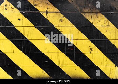 Schwarz-gelbe Streifen an der Wand. Warnschild - Stockfoto