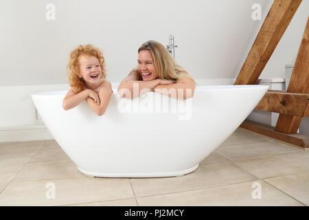 Mutter und Tochter auf der Suche über die Kante einer freistehenden Badewanne in ein modernes Bad - Stockfoto