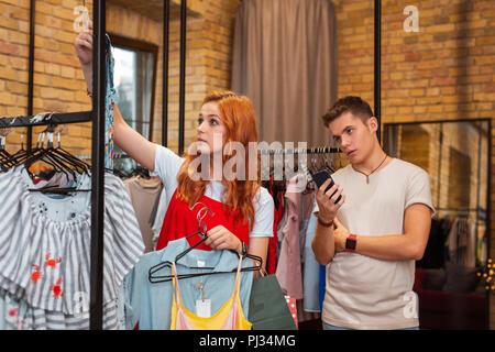 Müde Mann, Smartphone, während seine Freundin einkaufen, - Stockfoto