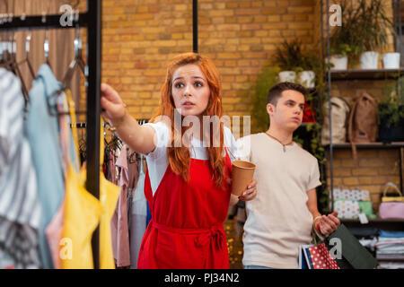 Junger Mann müde und seinen verrückten Freundin berühren Kleidung im Shop - Stockfoto