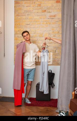 Müde mann Langeweile, während seine Freundin im Ankleidezimmer - Stockfoto