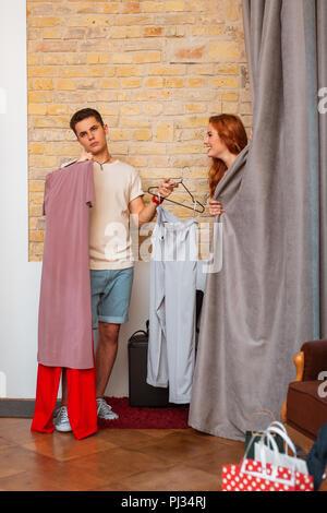 Erschöpft junge Mann stand in der Nähe der Umkleidekabine und wartet auf seine Freundin - Stockfoto
