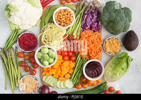 Oben Blick auf die Zutaten für den Salat, buntes Gemüse, Möhren, Zucchini, Kohl, Kichererbsen, Gurken und Tomaten, auf dem Holzbrett o - Stockfoto
