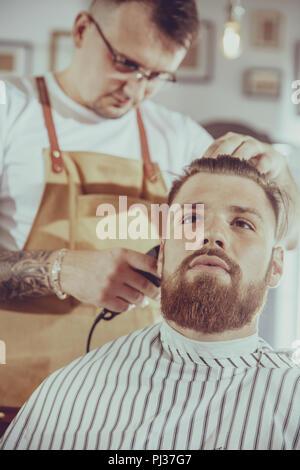 Mann beim Fräsen Haar in einem Barbershop - Stockfoto