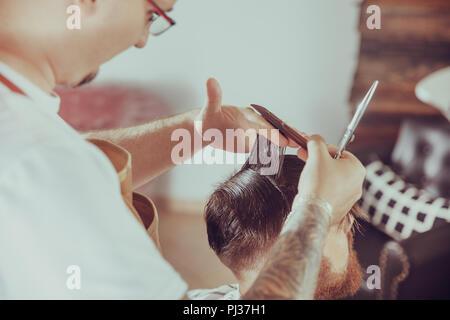 Friseur schneidet die Haare des Kunden in seinem Friseur. Foto im Vintage Style - Stockfoto