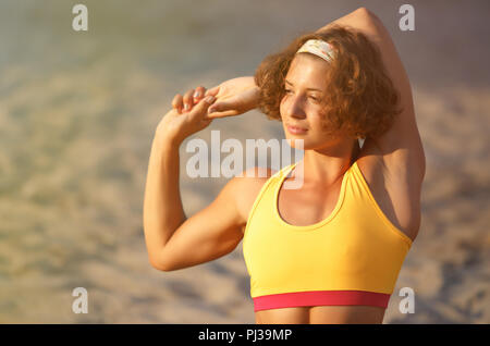 Porträt der schönen Athlet Mädchen mit starken Armen dehnen vor dem Training Outdoor. crossfit Frau in gelb Sport Top tragen ihren sollten - Stockfoto