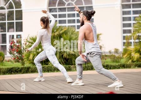 Sportliche Paare zusammen, die sich auf hohe städtische Gebäude. Sie sitzen auf Matten und biegen an der geraden weniger. Sie sind Finishing Krafttraining mit Hanteln - Stockfoto