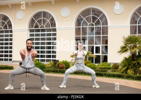 Sportliches Paar sind Wurmkuren gegen städtische Gebäude im Park - Stockfoto