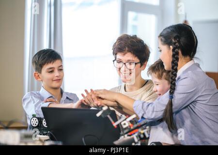 Glückliche Kinder Programmieren lernen mit Laptops auf außerschulische Klassen - Stockfoto