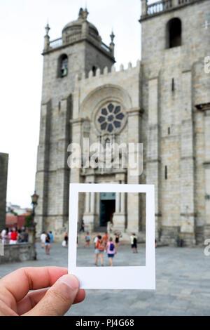 Nahaufnahme eines jungen kaukasischen Mann mit einem weißen Rahmen in seiner Hand vor der Kathedrale von Porto in Porto, Portugal, für die Simulation eines Instant Foto - Stockfoto