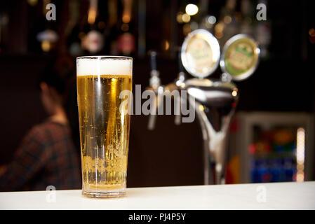Ein hohes Glas kaltes Bier mit Schaum und Blasen auf der Bar. - Stockfoto