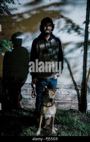 Porträt junger bärtiger Mann mit Hemd und Schatten der Bäume im Park mit pitbull Hund - Stockfoto