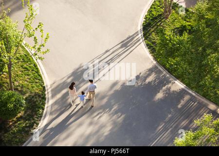 Glückliche junge Familie Hand in Hand gehen - Stockfoto