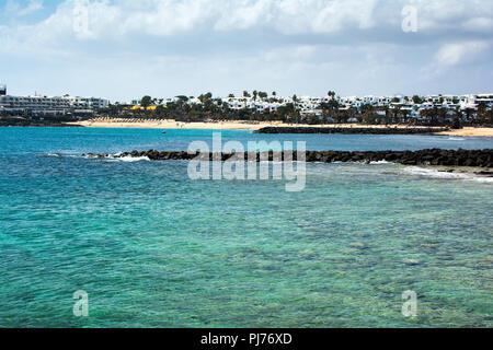 Türkisblaues Wasser und sandige Küste in Playa de Las Cucharas Strand in Costa Teguise, Lanzarote, Kanarische Inseln, selektiven Fokus - Stockfoto