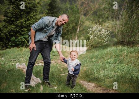 Portrait Vater und Sohn gehen auf grasigen Pfad - Stockfoto