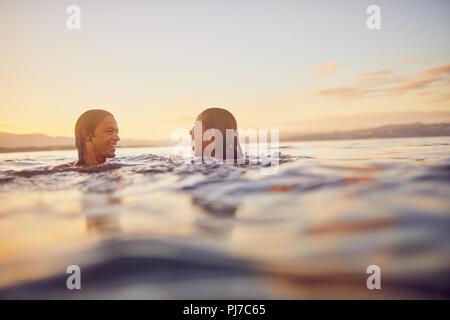 Junges Paar schwimmen im Meer bei Sonnenuntergang - Stockfoto