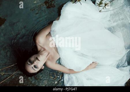 Frau am Ufer in weißem Kleid lügen, dunkle Geheimnis Szene - Stockfoto