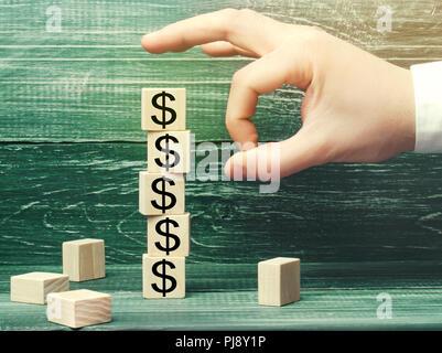 Geschäftsmann entfernt einen Cube mit einem Bild von Dollar. Die Finanz- und Wirtschaftskrise. kapitalabfluss. Sabotage der Wirtschaft. Konkurs. Druck auf - Stockfoto