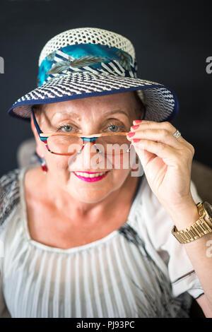 Elegante ältere Frau sitzt auf dem Sessel mit schwarzem Hintergrund - Stockfoto