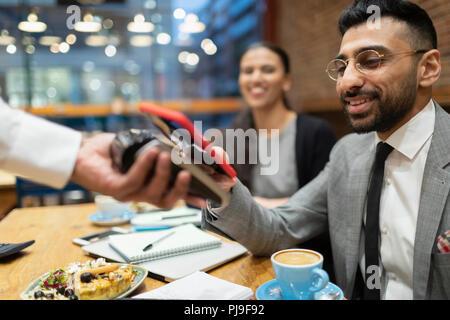 Unternehmer zahlen mit smart phone kontaktloses Bezahlen im Café - Stockfoto
