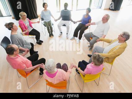 Aktive Senioren halten sich an den Händen im Kreis, meditieren im Community Center - Stockfoto