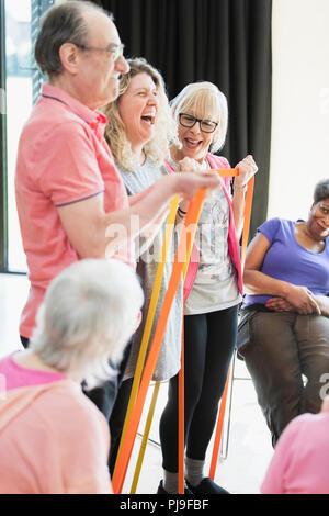 Lächelnd aktive Senioren und Instructor Stretching, das Training mit Bändern - Stockfoto