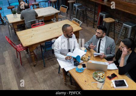 Unternehmen, die Menschen sprechen und Essen, Arbeiten im Cafe - Stockfoto
