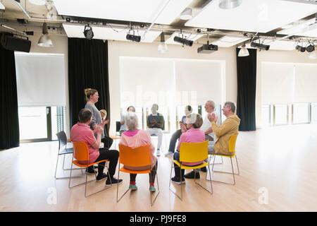 Aktive Senioren klatschen für Ausbilder im Kreis in der Mitte - Stockfoto