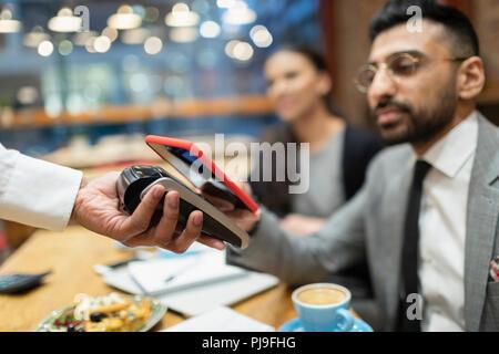 Unternehmer im Cafe bezahlen mit smart phone kontaktloses Bezahlen - Stockfoto