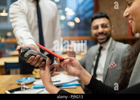 Geschäftsfrau bezahlen mit smart phone kontaktloses Bezahlen im Café - Stockfoto