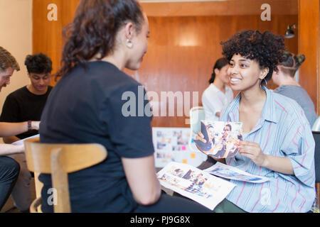 Lächelnde kreative weibliche Designer diskutieren Foto Beweise im Büro - Stockfoto
