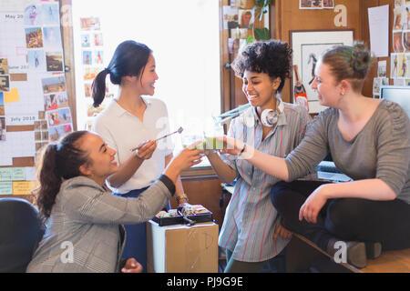 Kreative weibliche Designer toasten grüne Smoothies im Büro - Stockfoto