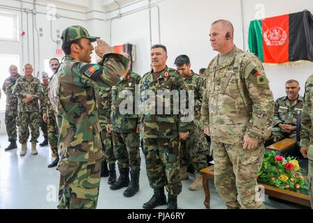 KANDAHAR, Afghanistan (Juli 5, 2018) - ein afghanischer Soldat, Links, begrüßt US-Armee Brig. Gen. Jeffrey Smiley, rechts, Kommandierender General für Zug, Beraten und Unterstützen Command-South, 5. Juli 2018, während der Eagle Strike Unternehmen Abschlussfeier in Camp Hero, Afghanistan. Eagle Strike Unternehmen ist eine neu gegründete Firma, die schnelle Eingreiftruppe aus afghanischen Soldaten in den verschiedenen Brigaden der 205th Korps, um zu helfen, die Letalität der afghanischen nationalen Verteidigungs- und Sicherheitskräfte zu erhöhen. - Stockfoto
