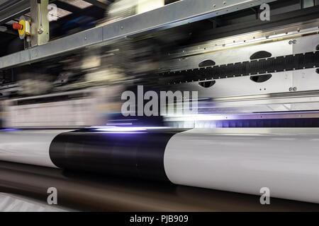 Gigantische Druckkopf vorbei über einen benutzerdefinierten Projekt auf Weiß glänzend Rollen. - Stockfoto