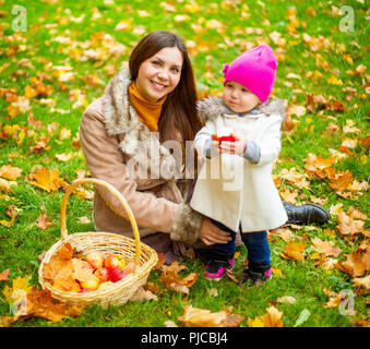 Glückliche Mutter und ihrem Baby bei einem Picknick im Herbst Park - Stockfoto