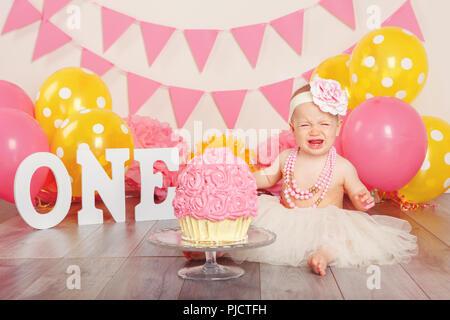 Portrait von Weinen umgekippt kaukasische Baby Mädchen in tutu Tüllrock feiert ihren ersten Geburtstag. Kuchen smash-Konzept. Kind sitzt auf dem Boden in Stu - Stockfoto