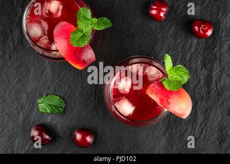 Ein Foto von zwei leuchtend roten Getränke mit Kirschen, Obst, und Minze auf Schwarz - Stockfoto