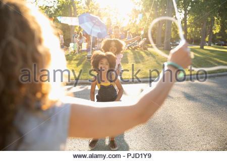 Schwestern, springen, abseilen am Sommer, der Nachbarschaft Block Party im sonnigen Straße - Stockfoto