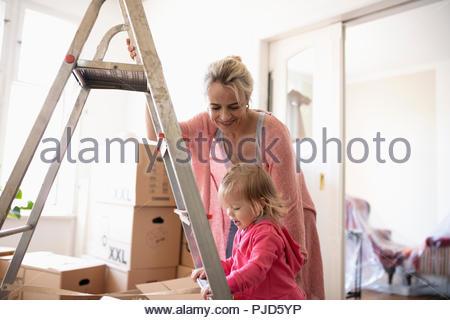 Mutter und Tochter an der Leiter, sich in die neue Startseite - Stockfoto
