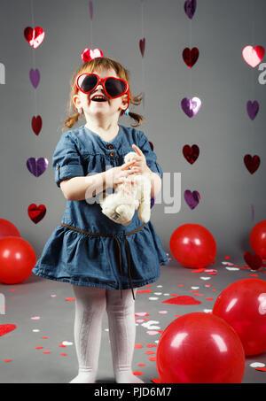 Portrait von cute adorable lächelnd Lustig weiß Kaukasische Mädchen Kleinkind im Studio mit roten luftballons herzen auf grauem Hintergrund tragen Lustig glasse - Stockfoto