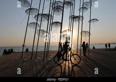 Frau radfahren Vergangenheit die Sonnenschirme, einen permanenten metallischen Installation von George Zoggolopoulos, in der nordgriechischen Hafenstadt Thessaloniki - Stockfoto