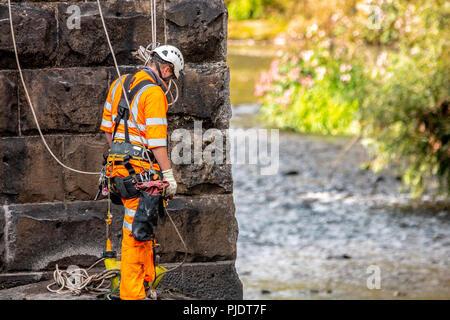 Rail Bridge Arbeiter befestigten Gurt tragen die vollständige PSA. - Stockfoto