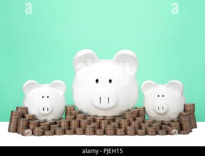 Drei Spardosen in Folge einer großen zwei kleine hinter einer Wand von Münzen in Stapeln. Wand von Einsparungen. Dollarzeichen in den Augen. Hellgrün hinterg Stockfoto
