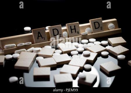Adhs in Scrabble Text mit weißem Verordnungpillen auf einem Schwarzen Tisch verschüttet geschrieben. Konzept der Aufmerksamkeit Defizit-Hyperaktivität-Störung Medikation - Stockfoto